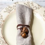 Acorn cording wrapped around a linen napkin in the middle of a dinner plate.