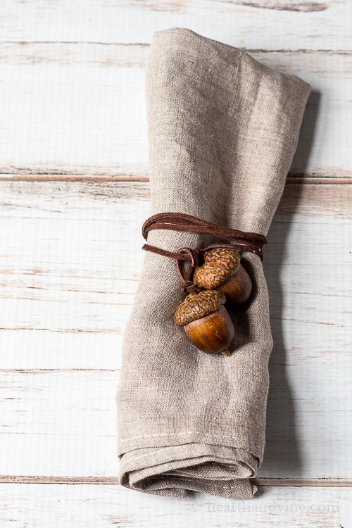 Linen tied with an acorn napkin tie made up of two real similar sized acorns and brown suede cording.