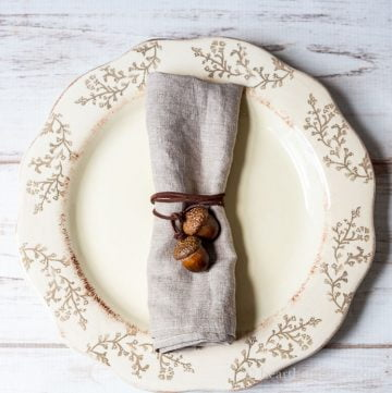 Acorn napkin tie around a linen napkin in the center of a dinner plate.