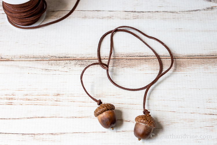 One acorn napkin tie in brown suede cording and two acorns on each end.