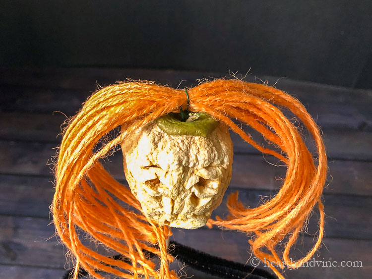 Orange twine pieces gather together in the middle with wire and pushed into the top of the dried apple head for hair.