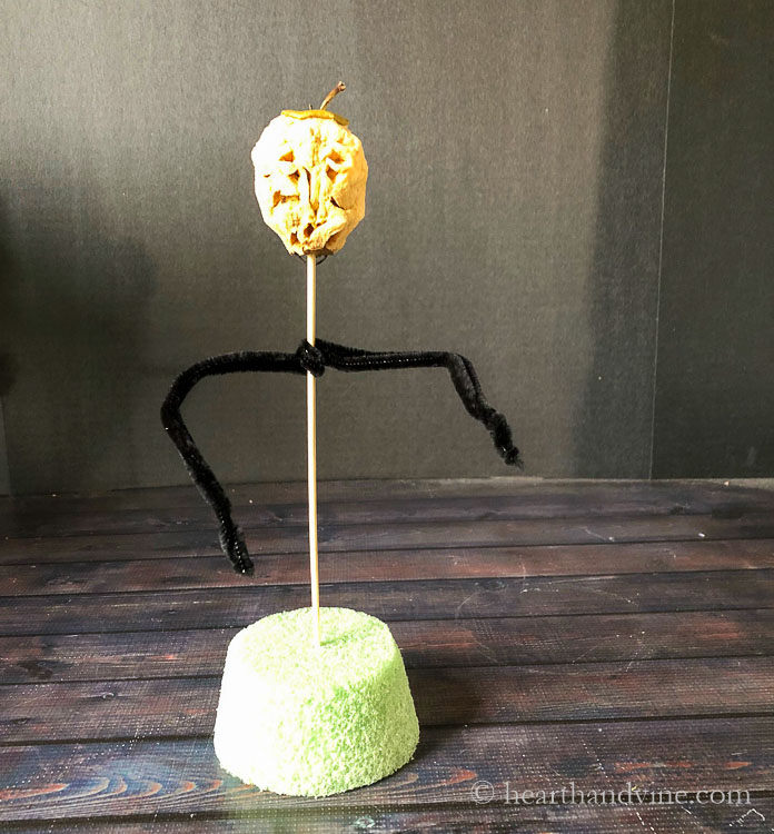 Apple head on top of a wooden skewer. Black pipe cleaners for arms and a round Styrofoam base.