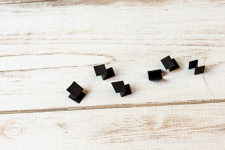 Little pieces of black card stock folded in an accordion style.