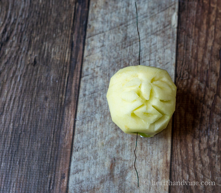Carved apple head with wire through the middle for hanging.