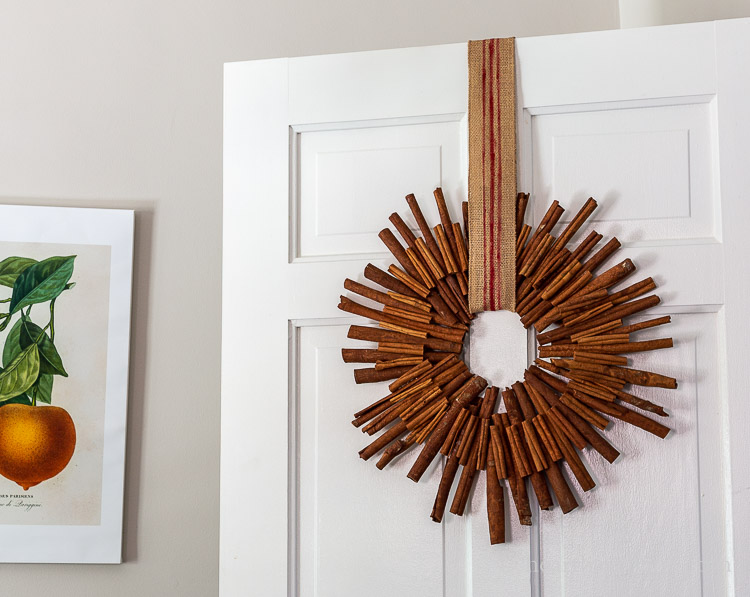 Cinnamon stick wreath hanging on a white door with a burlap ribbon striped in red paint.