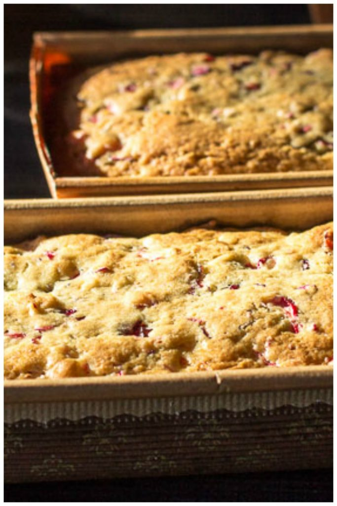Two loaves of cranberry orange bread in decorative paper loaf pans.