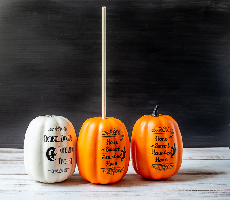 Three craft pumpkins. Two have the stems removed and the middle one has a large wooden dowel rod in the top.