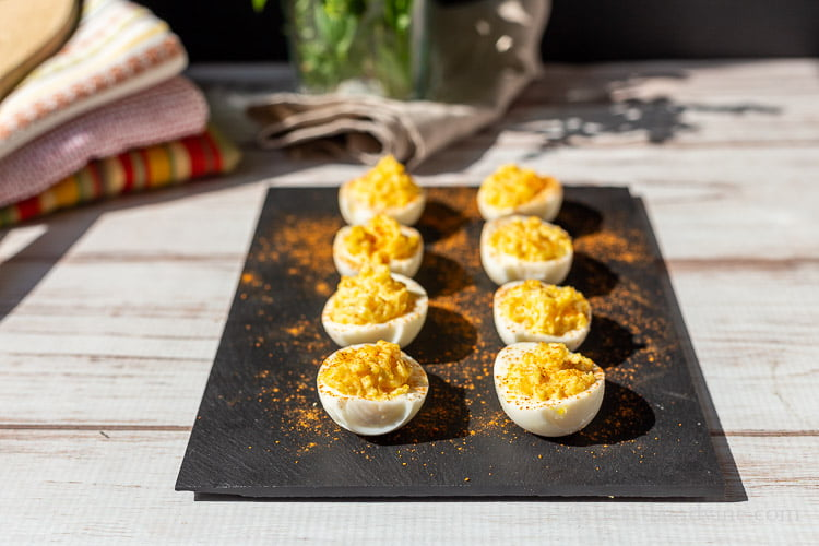 Eight deviled eggs on slate.