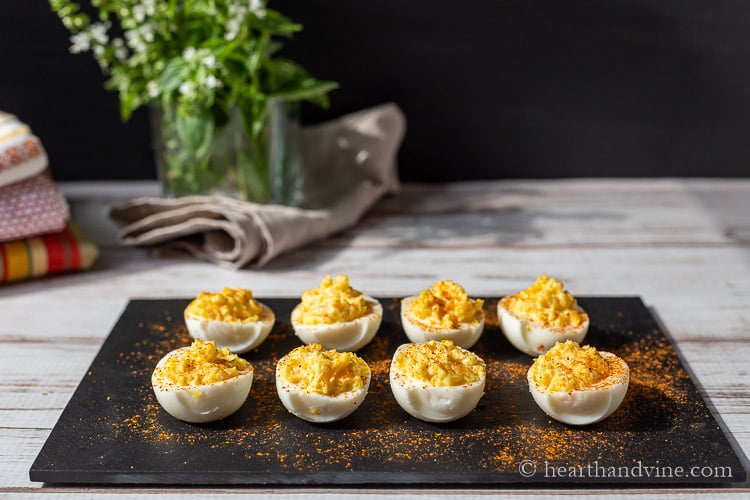 A slate tray displaying eight deviled eggs.