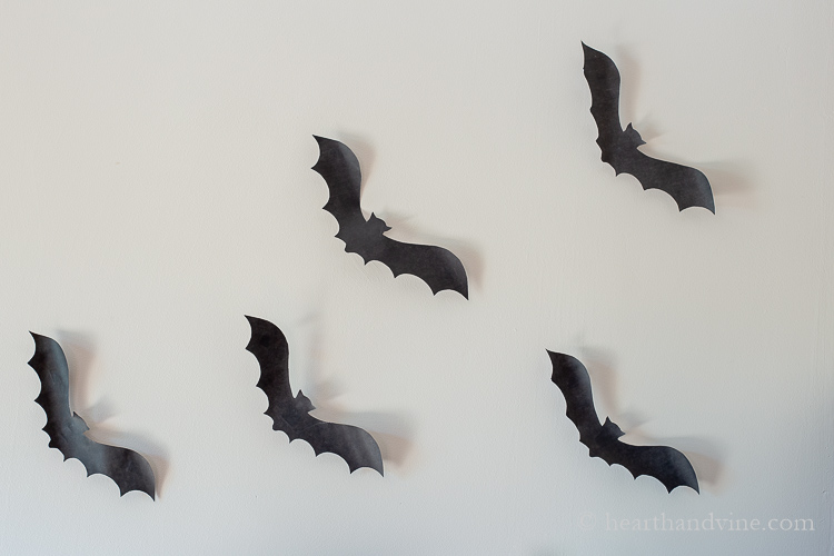 Paper bats taped to the wall to look like they are flying.
