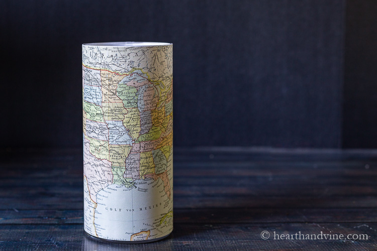 A tall glass vase cover with a map with a pillar candle inside.