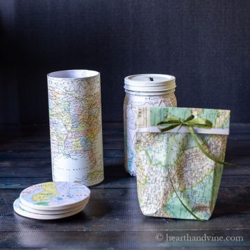 Four different crafts made with maps. Coaster, candle, bank and bag.