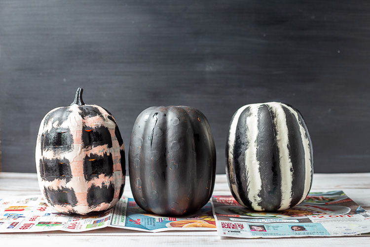 Three craft pumpkins with stickers, or masking tape that have been painted with black paint over top.