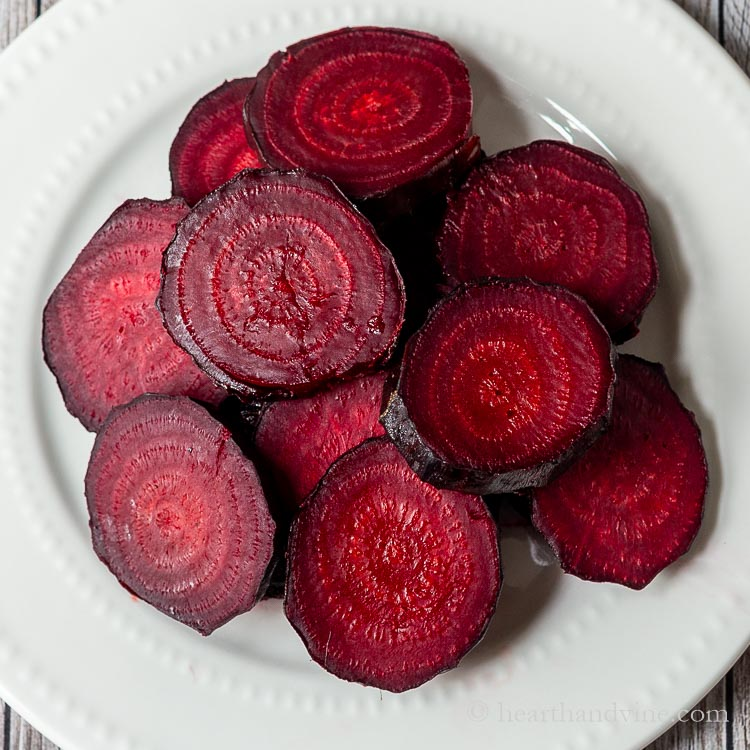 Sliced oven roasted red beets on a plate.
