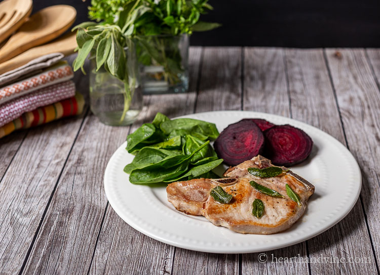 A plate with spinach, sliced red beets and a pork chop with sage leaves.
