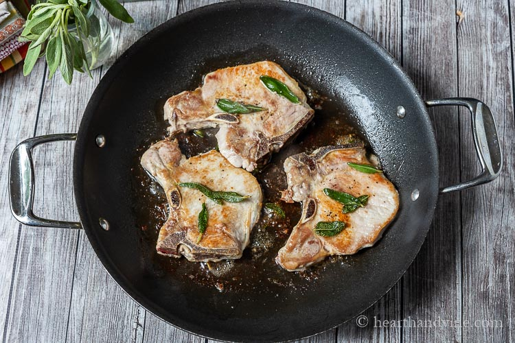 Three pork chops in a skillet with sage leaves on top.