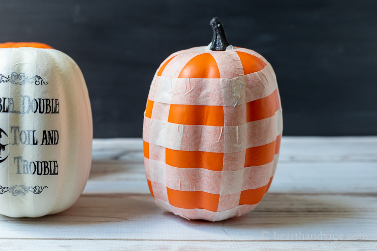 White craft pumpkin with vertical stripes of masking tape to the left and an orange pumpkin with masking tape in a plaid pattern.