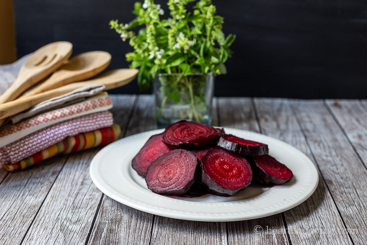 Oven roasted red beets on a plate in front of a jar of fresh basil leaves and next to a stack of kitchen towels and wooden spoons.