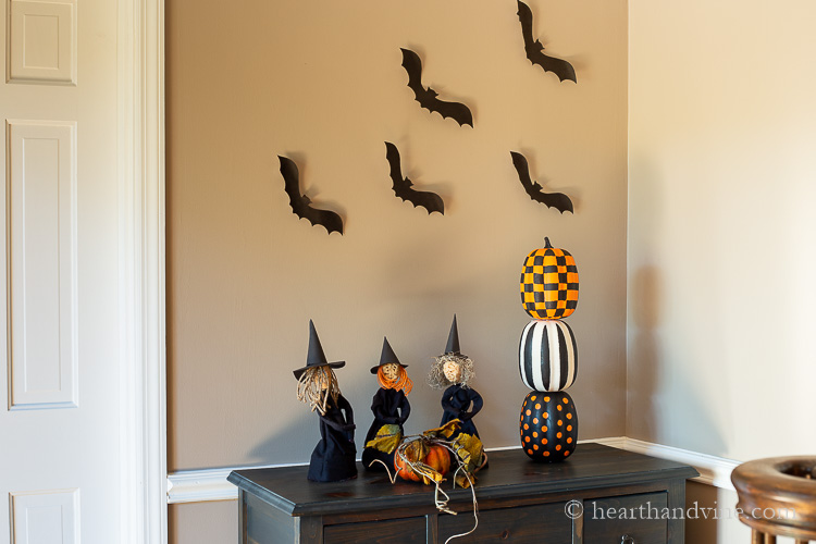 Halloween display with bats on the wall, apple head witches and graphic  stacked painted pumpkins on the dresser.