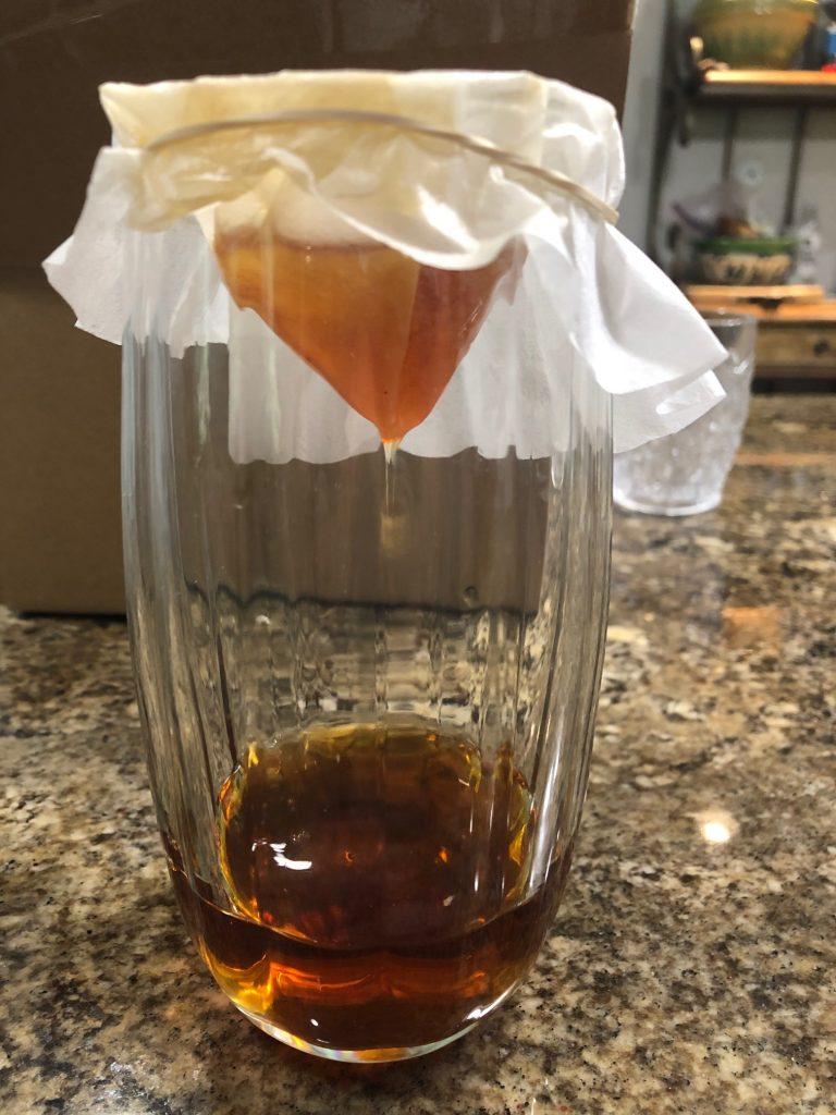 Straining vanilla extract into a mason