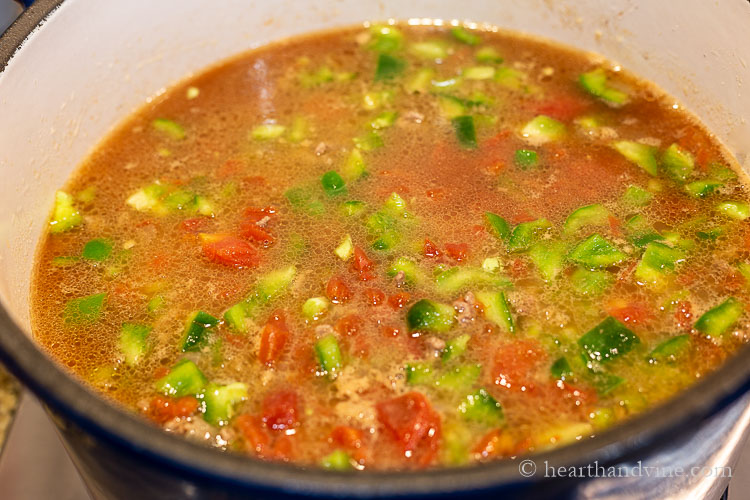 Stuffed pepper soup starting to cook in a large pot on the stove.