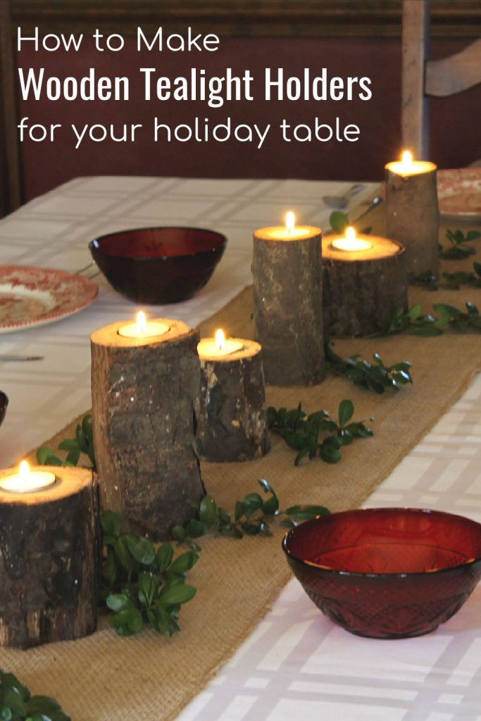 Dining table decorate with real wood logs with the top drilled out to hold tealights.
