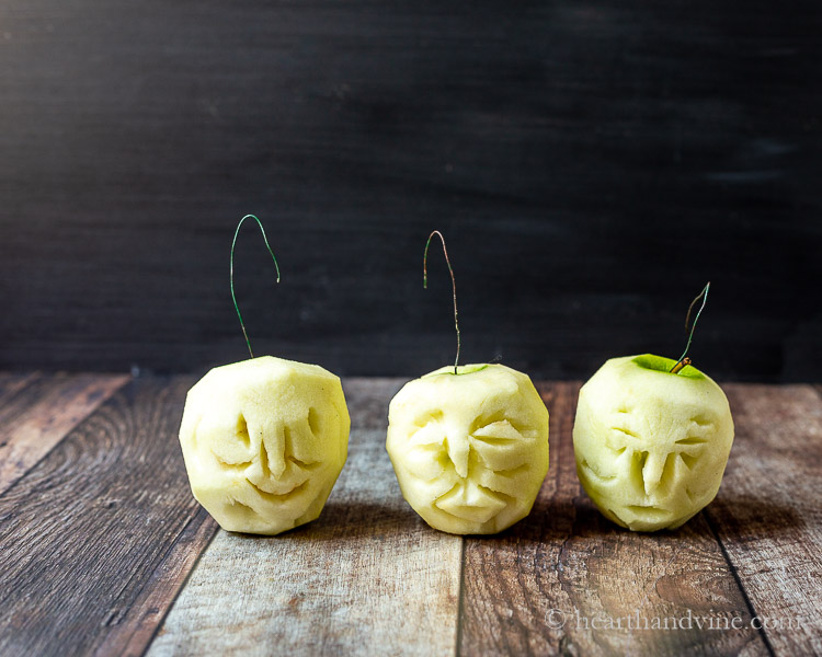 Three peeled apple carved into faces with wire hooks.
