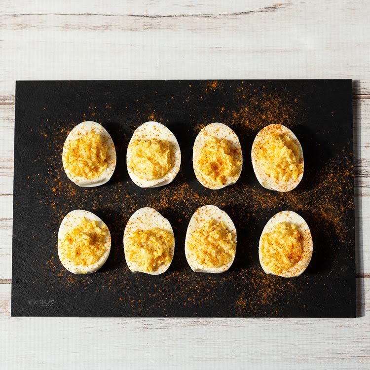 Two rows of deviled eggs with a ground paprika dusting.