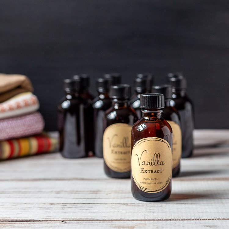 Bottles of homemade vanilla extract on a table next to a stack of kitchen towels.