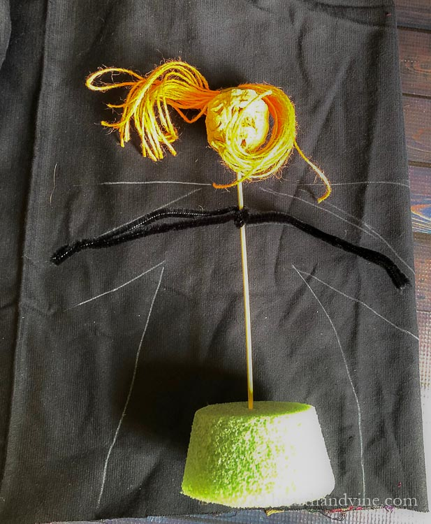 Apple head doll base on black fabric with chalk outline for doll dress.