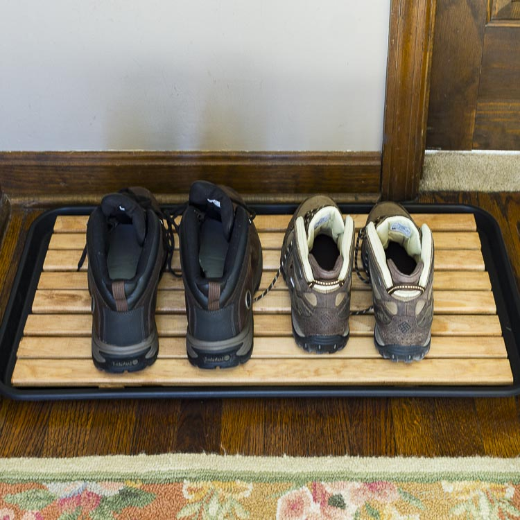 Wooden slat boot tray in foyer with two sets of boots.