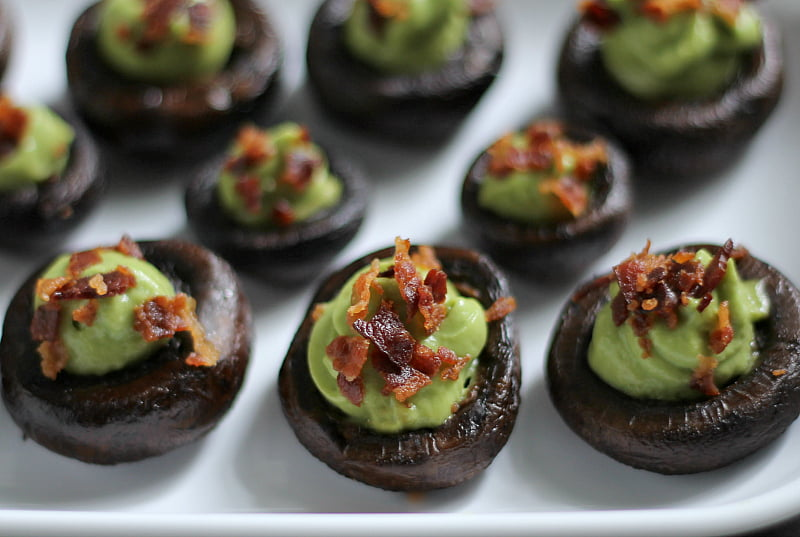 Tray of stuffed mushrooms with avocado cream and bacon.