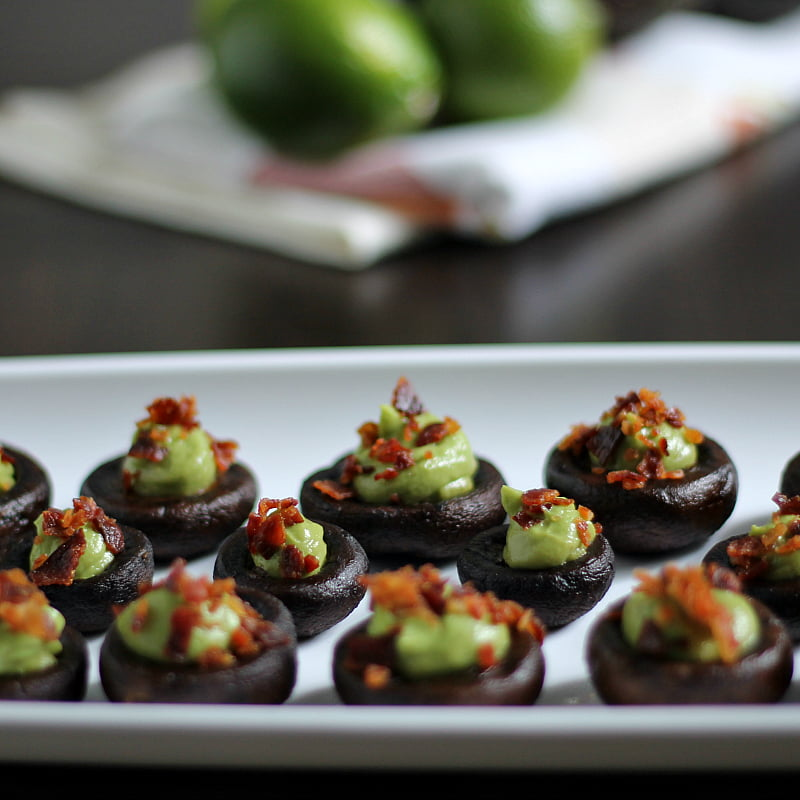 Long white tray filled with baked mushrooms stuffed with avocado cream and topped with bacon bits.