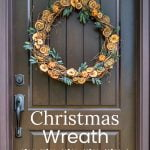 Dried fruit wreath with faux greenery on brown door.