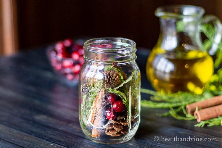 Mason jar stuffed with cranberries, cinnamon sticks, pine cones and cedar.