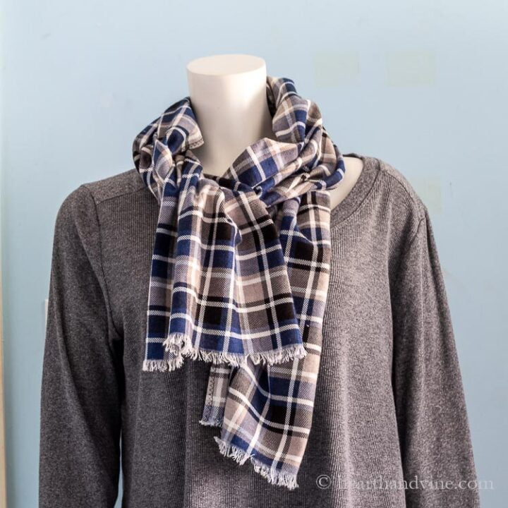 Blue black gray and white plaid flannel scarf on a mannequin