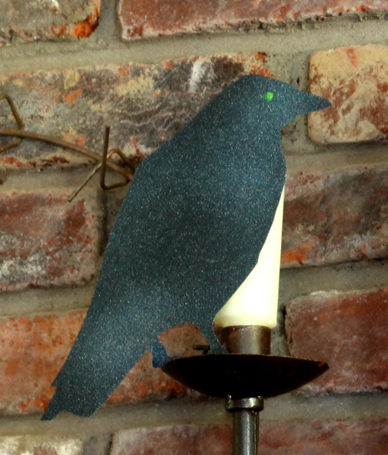 Halloween black crow with glowing green eye on mantel.