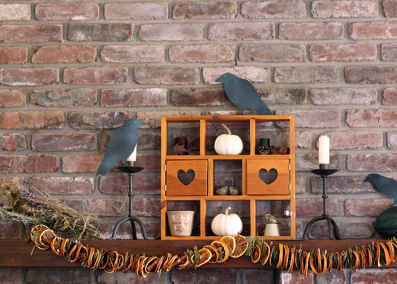 Family mantel decorated for Halloween with dried fruit, pumpkins and paper crows.