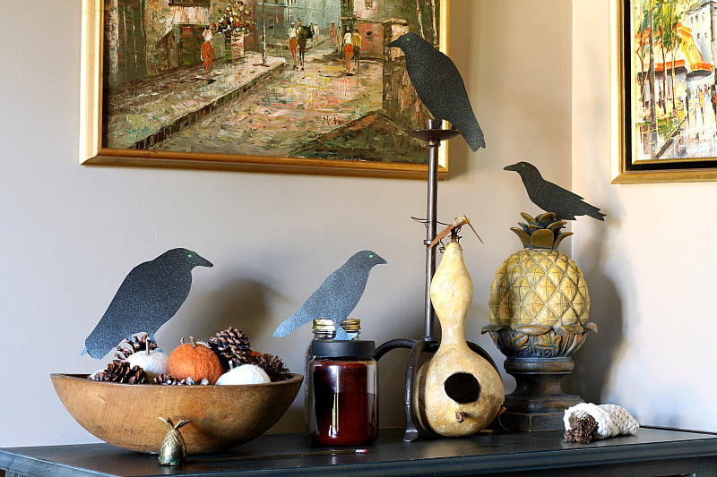Black paper birds with glitter and green eyes sitting on items on a foyer chest.