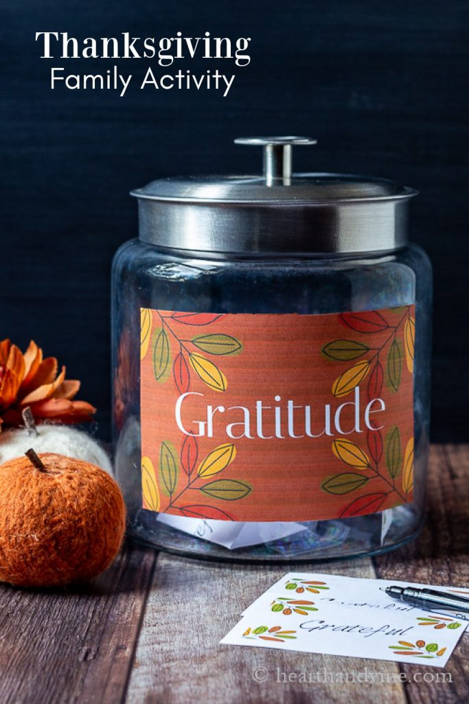 Fall colored gratitude jar on a table with a lid, filled with paper cards.