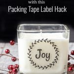 Square candle with the word Joy surrounded by a wreath on the front in a clear label with black lettering.
