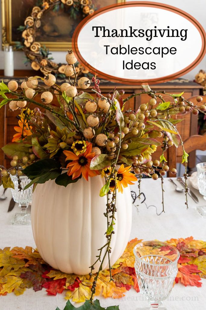 Pumpkin vase centerpiece sitting on a colorful fall leaf table runner.
