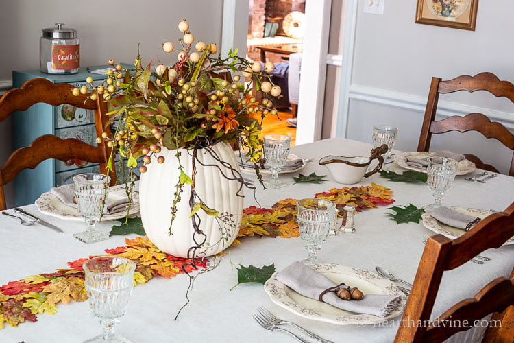 Partial view of Thanksgiving table with a white pumpkin vase filled with artificial autumn flowers on a colorful leaf runner and a gratitude jar in the background.
