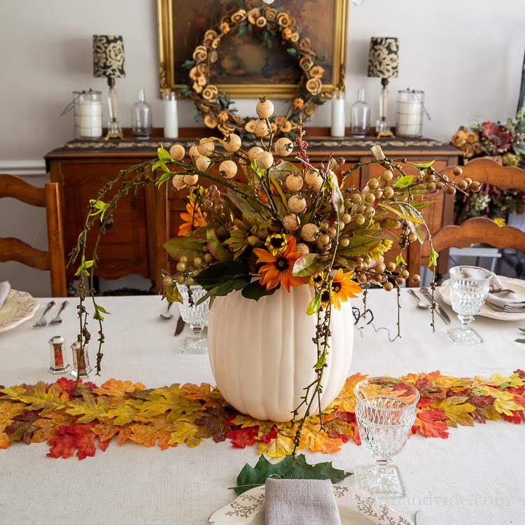 Decorated Thanksgiving table with pumpkin vase filled with flowers, a leaf runner and real oak leaves.