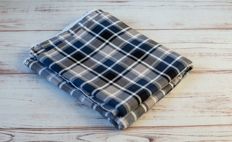 Two yards of blue, black, gray and white plaid flannel fabric.