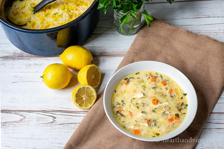 Large pot of soup, and lemons next to a bowl of lemon chicken orzo soup. Also a jar of parsley in water.