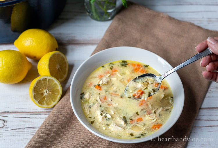 Lemons next to a bowl of lemon chicken orzo soup with a spoonful of the soup.
