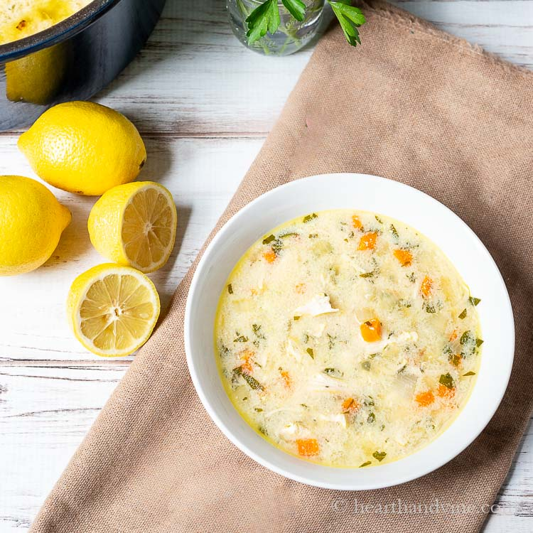 Bowl of lemon chicken Greek orzo soup next to some lemons and the corner of the pot of soup.