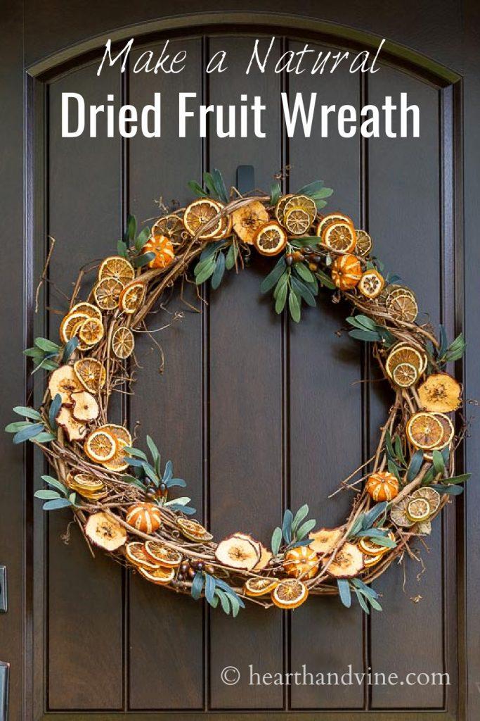 Dried fruit wreath hanging on brown front door.