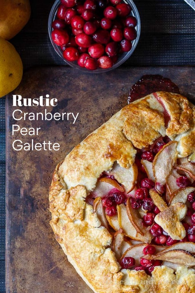 A partial view of a cranberry pear galette on a baking stone.